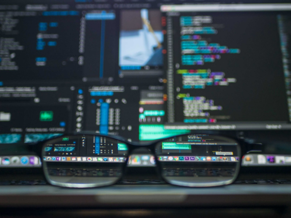 glasses in front of a blurred computer screen, making the question of tokenization vs encryption more clear