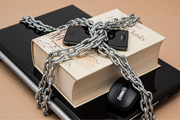 chains locking up a computer, phone, and book, to represent a tokenization vault